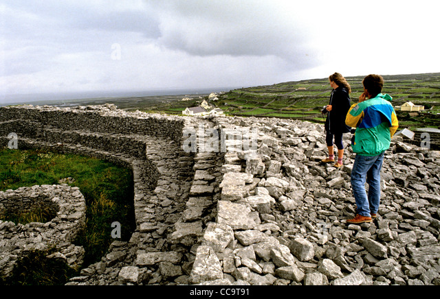 Two visitors explore one of a number of Iron Age forts on the Aran Islands. This one is in Inis Oirr - Stock-Bilder