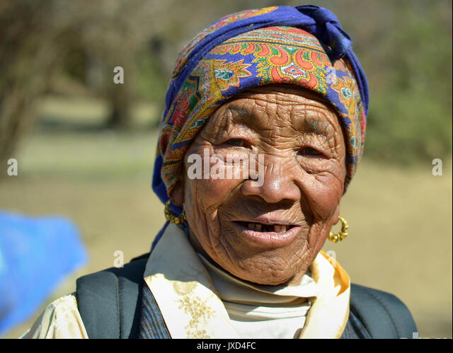 Closeup street portrait (outdoor headshot, full-face view) of an old Sherpa woman with traditional golden earrings; - Stock Image