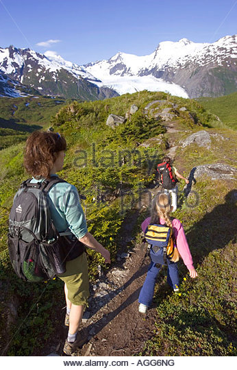 Mother daughters hiking Portage Pass Trail towards Portage Glacier Chugach Mtns Nat Forest Alaska - Stock Image