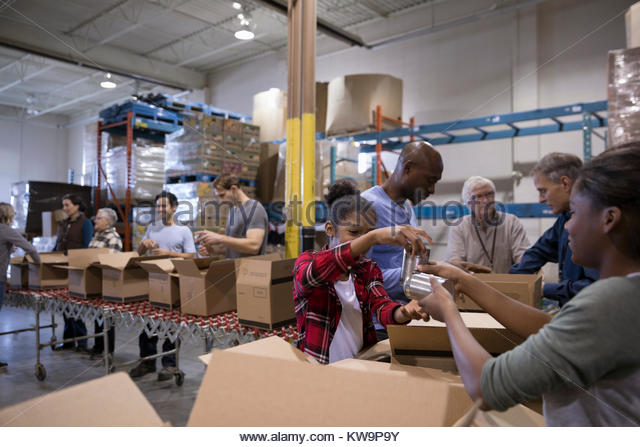 Volunteers filling boxes for food drive in warehouse - Stock Image