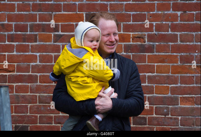 The Honourable Ben Gummer MP smiling and holding an unhappy child that very probably is his son - Stock Image
