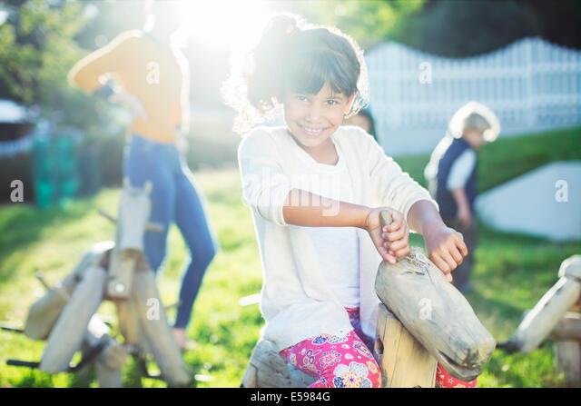 Girl smiling on rocking horse in playground - Stock Image
