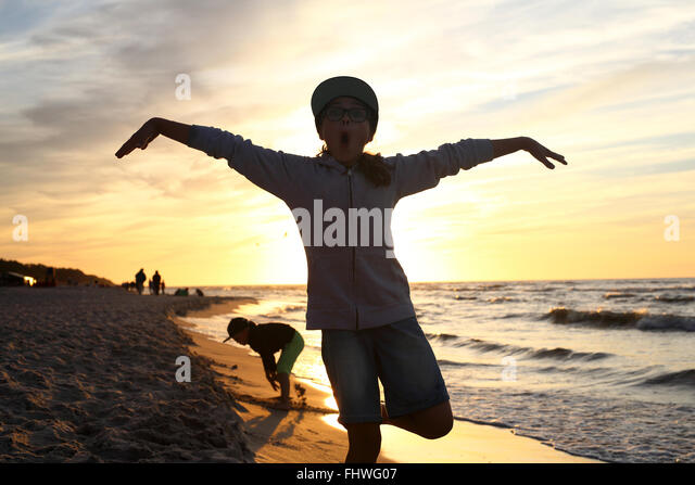 Holiday! The girl jumps high on a sandy beach - Stock Image