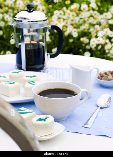 serving of coffee and sweets garden side - Stock Image