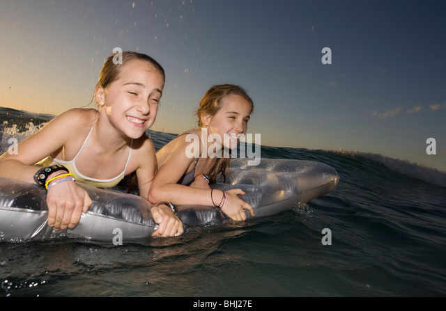 Twin sisters wave surfing on airbed - Stock-Bilder