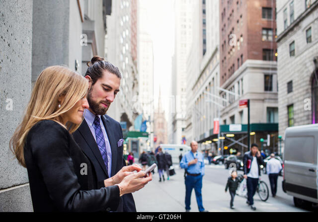 Woman showing phone to businessman against buildings in city - Stock-Bilder