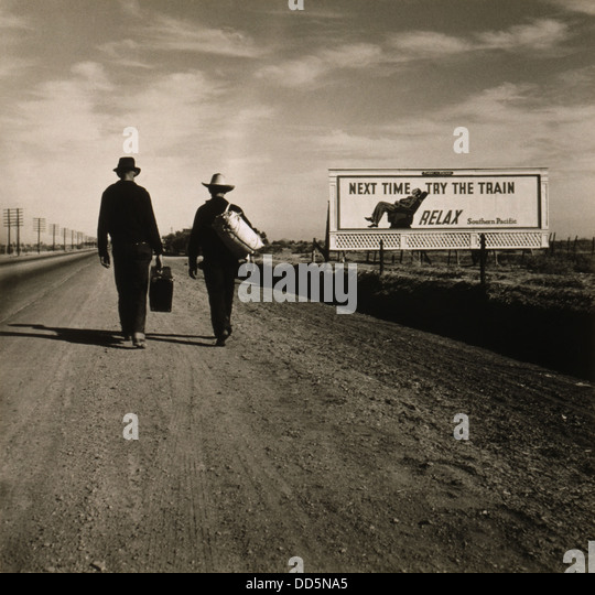 Two men walking toward Los Angeles, March 1937. Ahead of them is a Southern Pacific Railroad billboard reading, - Stock Image