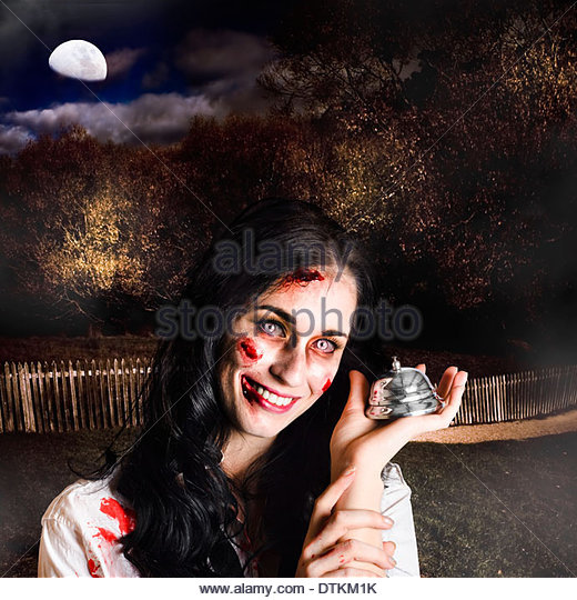 Creepy deceased zombie woman holding silver service bell in a spooky graveyard location in a depiction of death - Stock Image
