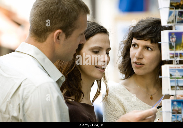 Tourists looking at postcards - Stock Image