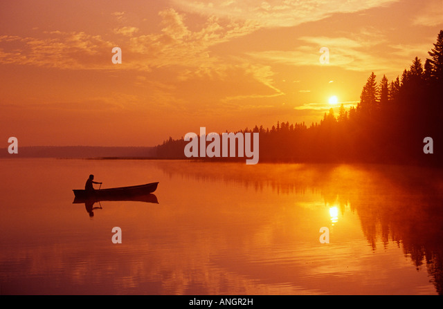 Canoeing on Child's Lake at sunrise reflection, Duck Mountain Provincial Park, Manitoba, Canada. - Stock Image