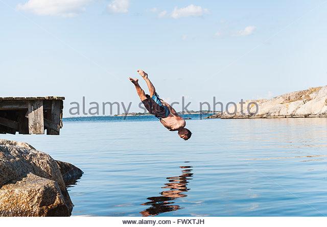 Sweden, Stockholm archipelago, Uppland, Vidinge, Man jumping into lake from jetty - Stock Image