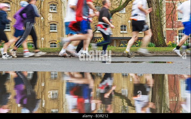 marathon runners reflected in puddle - Stock Image