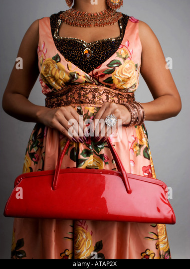 WOMAN HOLDING HER RED PURSE - Stock Image