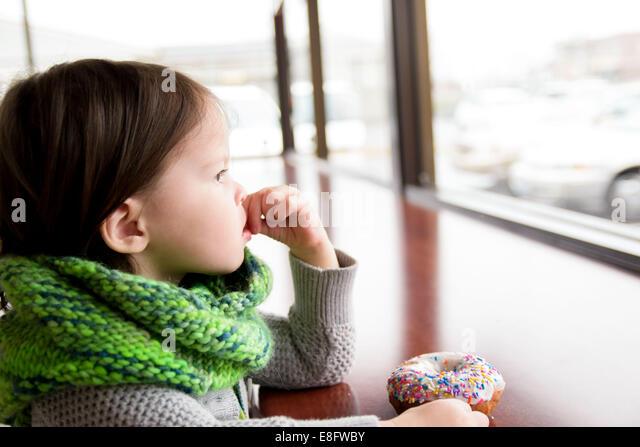 Girl with donut (2-3 years) - Stock-Bilder