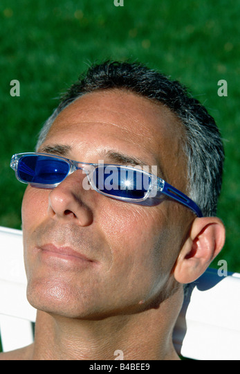 Head and Shoulders Portrait of a Man Soaking in the Sun He is Wearing Sunglasses - Stock Image