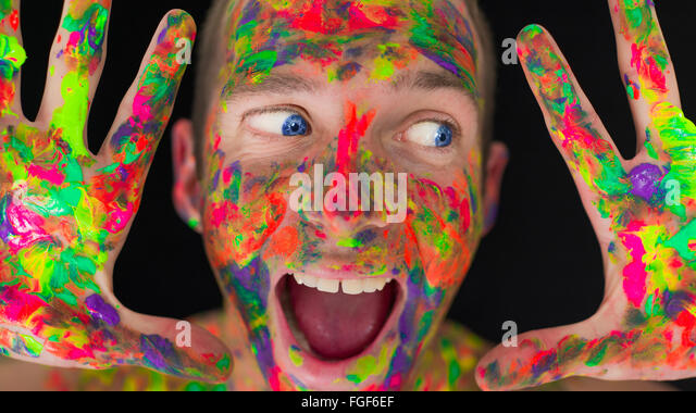 Close up of a man's face covered in coloured paint - Stock Image