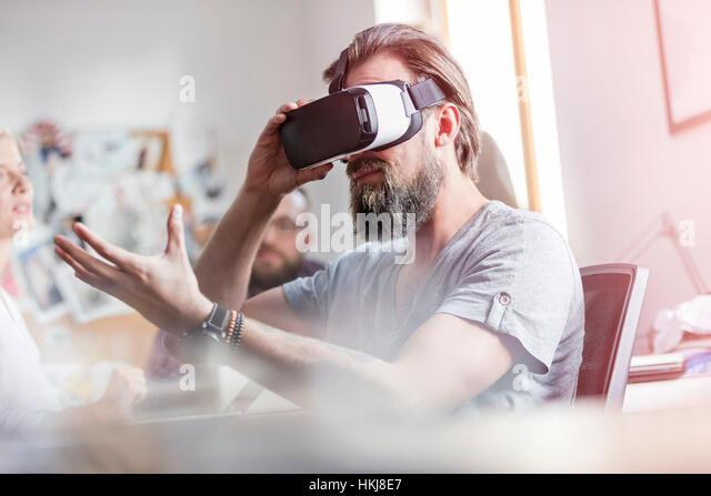 Male design professional using virtual reality simulator glasses in office - Stock-Bilder