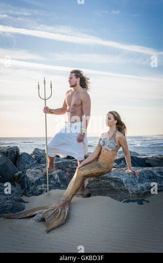 King Neptune and a mermaid on rocks by the beach, Virginia Beach, VA - Stock Image