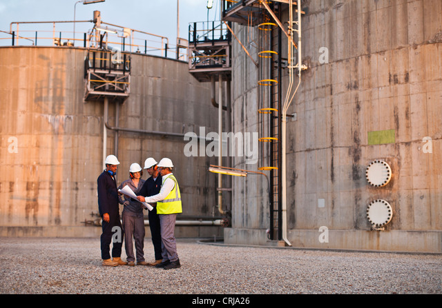 Workers reading blueprints at plant - Stock Image