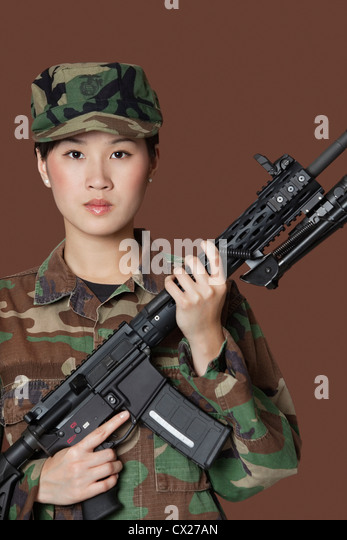 Us marine corps soldier holding m4 assault rifle over brown background - Beautiful Young Women Gun Stock Photos Amp Beautiful Young