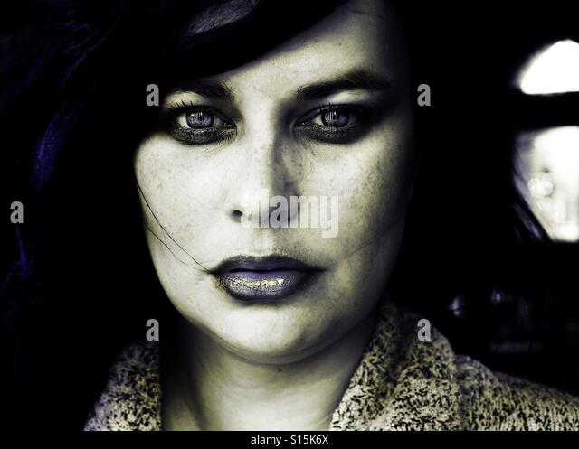 Dark portrait of young woman looking at camera - Stock-Bilder