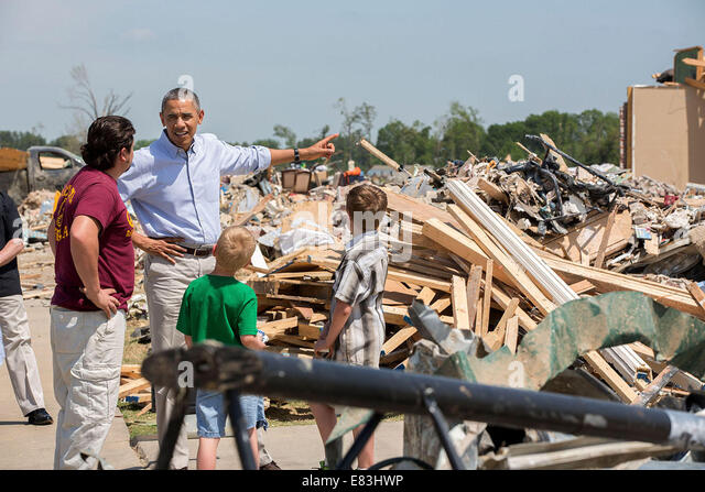 President Barack Obama talks with tours the wreckage of a tornado-damaged neighborhood in Vilonia, Ark., May 7, - Stock Image