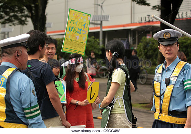 Japanese police monitor an anti-nuclear protest march in Shibuya, Tokyo. - Stock Image