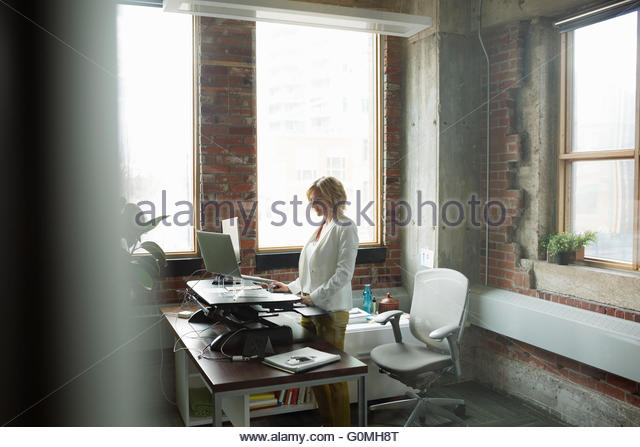 Businesswoman using computer sit-stand desk in office - Stock Image