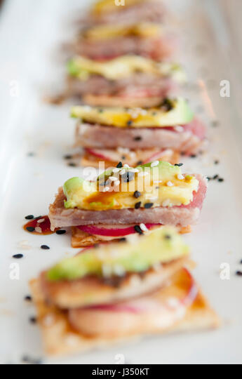 Closeup of ahi tuna appetizer, with avocado and radish on crackers, served on a white plate - Stock Image