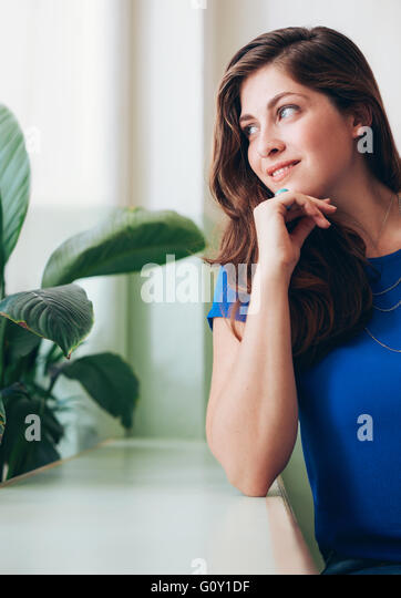 Portrait of beautiful young woman sitting at a counter. Caucasian female sitting with her hands on chin and looking - Stock Image