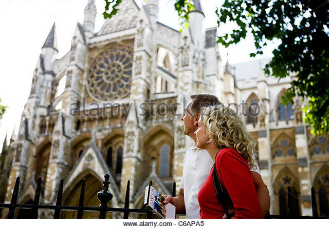 A middle-aged couple looking at Westminster Abbey, London - Stock Image