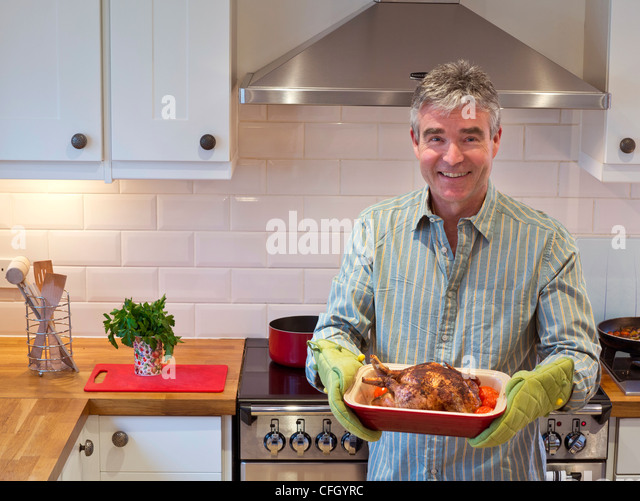 Smiling relaxed confident mature man in contemporary kitchen presents a hot freshly cooked meal of roast chicken - Stock-Bilder