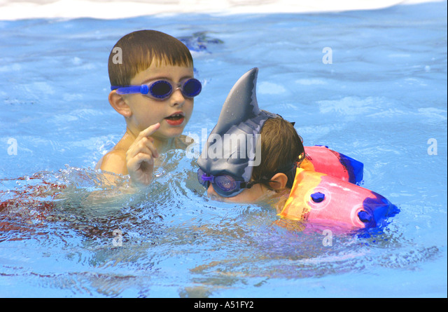 Swimming pool young boy girl playing blue goggles shark fin hat family summer vacation - Stock Image