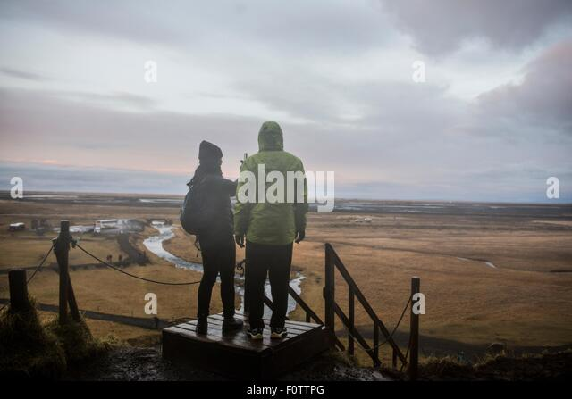 Male and female tourists taking photographs from viewing platform at Seljalandsfoss, Iceland - Stock Image