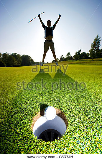 A golfer leaps into the air to celebrate a winning put. - Stock-Bilder