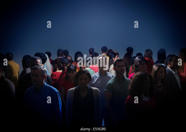 Crowd turning back on bright light - Stock Image