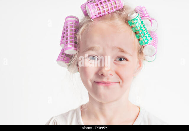 Portrait of emotional cute little girl with curler - Stock Image