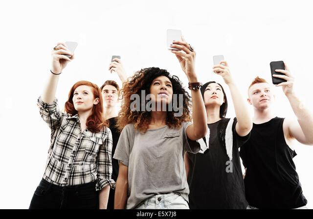 Studio portrait of five young adults taking selfies on smartphones - Stock Image
