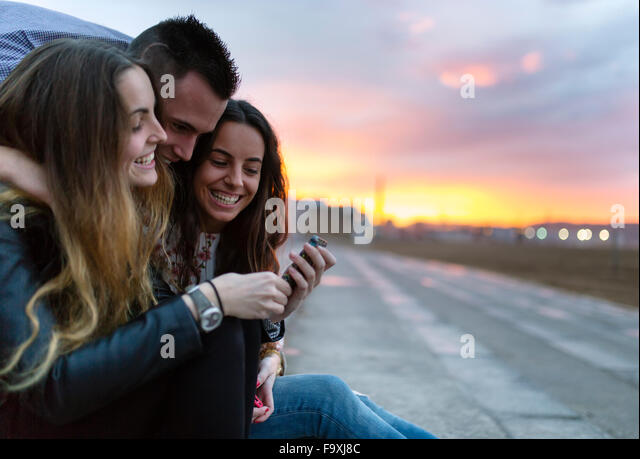 Three happy friends at evening twilight - Stock Image