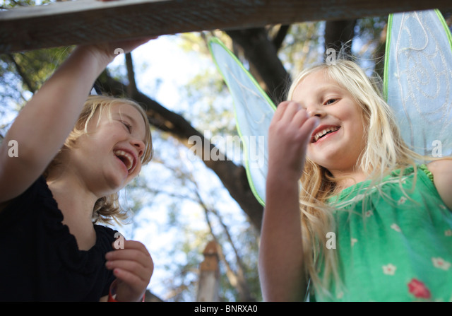 Girls playing dress up laughing. - Stock Image