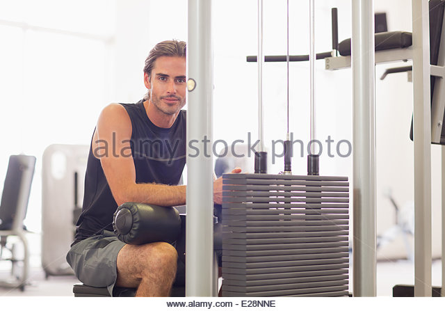 Portrait of smiling man using exercise equipment in gymnasium - Stock Image