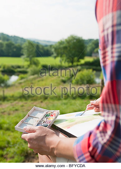 Woman on gate painting picture - Stock Image