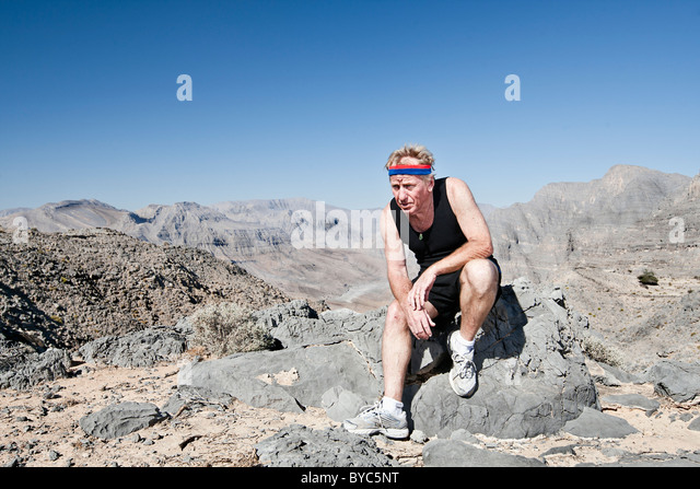 Senior Male (60s) running in Oman Mountains. - Stock Image