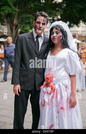Couple dressed up in macabre outfits in Zocalo (plaza) for Day of the Dead celebration in Oaxaca, Mexico. - Stock Image