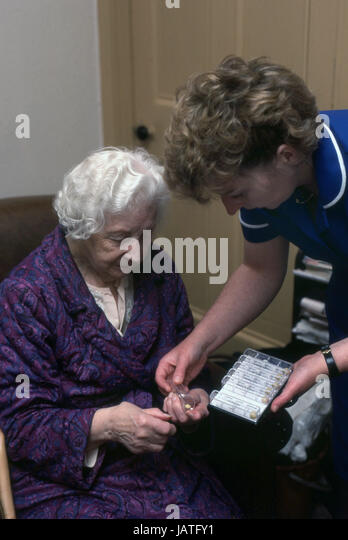 district nurse on a home visit assisting elderly woman with her daily medication - Stock Image