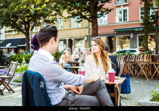 Friends sitting at sidewalk cafe in town square - Stock Image