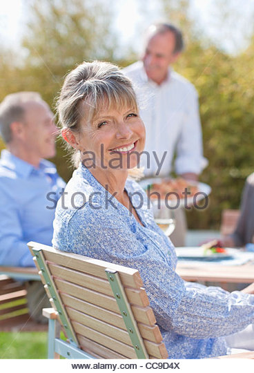 Portrait of smiling senior woman enjoying lunch at table in sunny garden - Stock Image