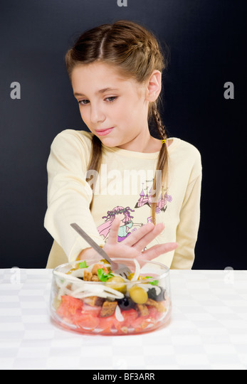 Close-up of a girl pushing a bowl of salad away - Stock Image