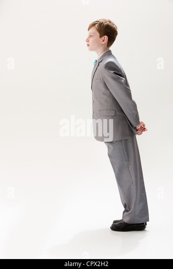Boy wearing grey suit, studio shot - Stock Image