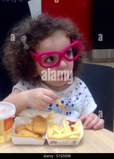 Little girl eating McDonalds - Stock-Bilder